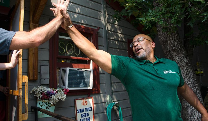 """ADVANCE FOR WEEKEND EDITIONS, AUG 19-20 - In this Aug. 12, 2017 photo, Dave """"Big Dave"""" Sylvester high-fives patrons entering the Pickle Barrel in Bozeman, Mont., as part of his nationwide hug and high-five tour. (Freddy Monares/Bozeman Daily Chronicle via AP)"""