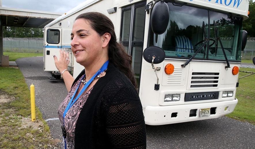 In this Tuesday, Aug. 8, 2017 photo, Jane Calabrese, counselor re-entry program with John Brooks Treatment Center, poses near a mobile clinic in Atlantic City, N.J. One by one, inmates at the Atlantic County Justice Facility made their way outside in a secured area on a recent Wednesday and stepped into a bus from the John Brooks Recovery Center for their daily dose of methadone. The inmates are the first in the state to get methadone, a medication assisted treatment for opioid addiction, from a mobile service while behind bars. (Edward Lea/The Press of Atlantic City via AP)