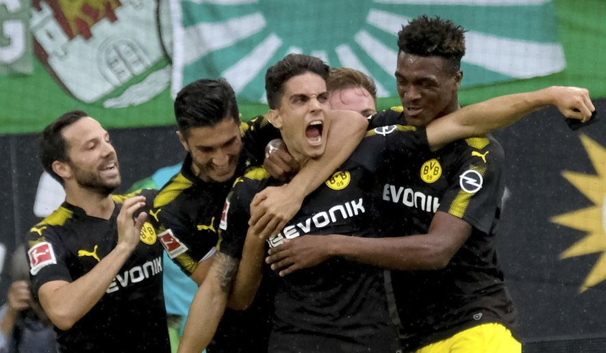 Dortmund's Marc Bartra, third left, celebrates his goal together with Gonzalo Castro. left,  Nuri Sahin, second left,  and Dan-Axel Zagadou, right,  during the German Bundesliga soccer match between VfL Wolfsburg and Borussia Dortmund in  Wolfsburg, Germany, Saturday, Aug. 19,  2017. (Peter Steffen/dpa via AP)