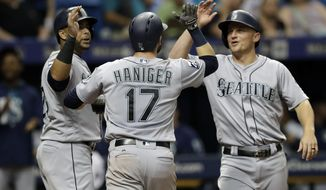 Seattle Mariners' Mitch Haniger, center, celebrates with Kyle Seager, right, and Nelson Cruz left, after Haniger hit a grand slam off Tampa Bay Rays starting pitcher Jake Odorizzi during the third inning of a baseball game Saturday, Aug. 19, 2017, in St. Petersburg, Fla. (AP Photo/Chris O'Meara)
