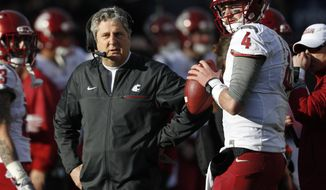FILE - In this Nov. 19, 2016, file photo, Washington State head coach Mike Leach, left, confers with quarterback Luke Falk during an injury time out against Colorado in the first half of an NCAA college football game in Boulder, Colo. As college football season approaches teams all over the country are choosing captains, those hard-working, high-character players who set an example for their teammates to follow through both actions and words. (AP Photo/David Zalubowski, File)