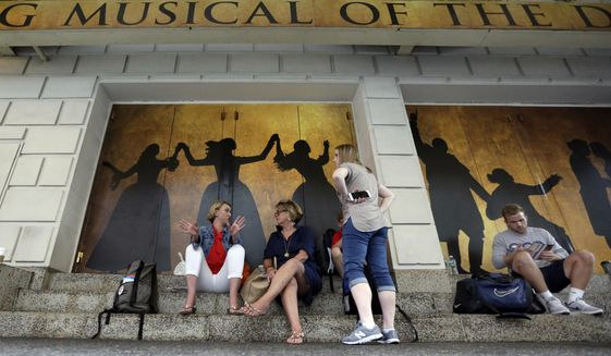 """People wait in the ticket cancellation line for a chance to see the Broadway show """"Hamilton"""" at the Richard Rogers Theatre, in New York's Theater District, Friday, Aug. 18, 2017. The still incredibly popular show """"Hamilton"""" announced this week that it would be the latest to offer up a new block of tickets for sale using new technology, called """"Verified Fan,"""" to try to keep re-sellers and brokers from snapping them all up. (AP Photo/Richard Drew)"""