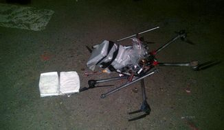 In this image released by the Tijuana Municipal Police on Wednesday, Jan. 21, 2015, a drone loaded with packages containing methamphetamine lies on the ground after it crashed into a supermarket parking lot in the city of Tijuana on Tuesday, Jan. 20, 2015. According to police, six packets of the drug, weighing more than six pounds, were taped to the six-propeller remote-controlled aircraft. (AP Photo/Secretaria de Seguridad Pública Municipal de Tijuana) ** FILE **