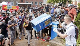 In this Aug. 12, 2017 file photo, white nationalist demonstrators, right, clash with a counter demonstrator as he throws a newspaper box at the entrance to Lee Park in Charlottesville, Va. The deadly white nationalist demonstration in Virginia has brought new attention to an anti-fascist movement whose black-clad, bandana-wearing members have been a regular presence at protests around the country in the last year. Members of the antifa movement were among those protesting the Charlottesville rally last weekend. (AP Photo/Steve Helber, File)