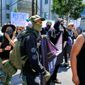 A masked group of demonstrators join in a protest against racism in the Venice beach area of Los Angeles on Saturday, Aug. 19, 2017. The peace and unity gathering was held Saturday morning at the beach south of Los Angeles in response to the deadly events at a white nationalist gathering in Charlottesville, Virginia. (AP Photo/Richard Vogel)