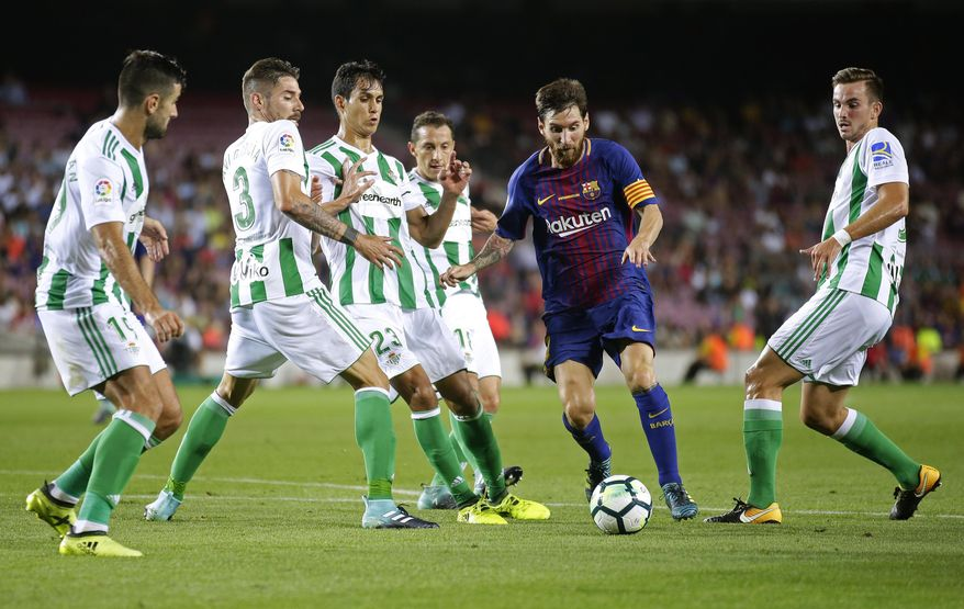 FC Barcelona's Lionel Messi, second right, in action during the Spanish La Liga soccer match between FC Barcelona and Betis at the Camp Nou stadium in Barcelona, Spain, Sunday, Aug. 20, 2017. (AP Photo/Manu Fernandez)