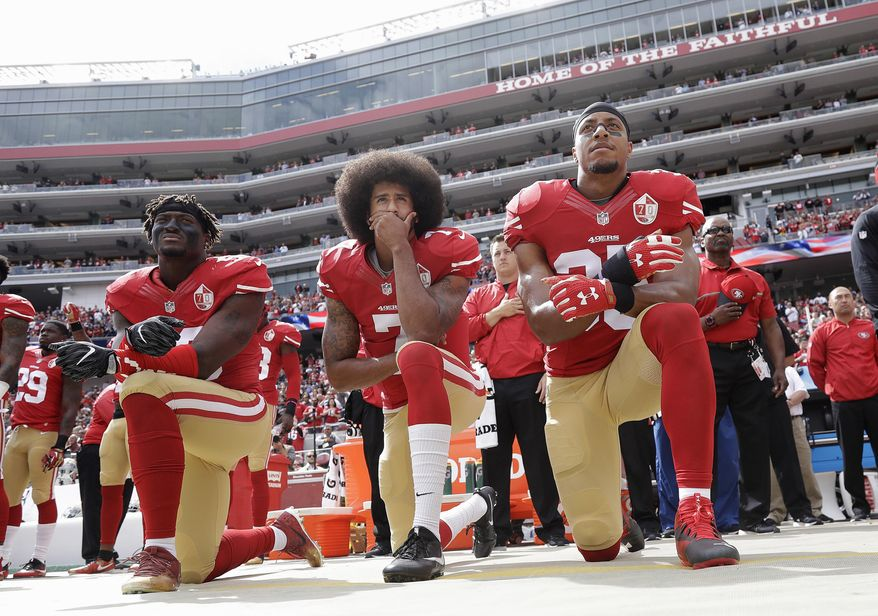 FILE - In this Oct. 2, 2016, file photo, from left, San Francisco 49ers outside linebacker Eli Harold, quarterback Colin Kaepernick, center, and safety Eric Reid kneel during the national anthem before an NFL football game against the Dallas Cowboys in Santa Clara, Calif. What started as a protest against police brutality has mushroomed a year later into a divisive debate over the future of Kaepernick who refused to stand for the national anthem and now faces what his fans see as blackballing for speaking out in a country roiled by racial strife. The once-rising star and Super Bowl quarterback has been unemployed since March, when he opted out of his contract and became a free agent who could sign with any team. (AP Photo/Marcio Jose Sanchez, File)