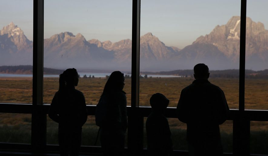 In this Aug. 28, 2016 file photo, visitors watch the morning sun illuminate the Grand Tetons, partially-obscured by smoke from nearby wildfires, as seen from within the Great Room at the Jackson Lake Lodge, in Grand Teton National Park, north of Jackson Hole, Wyo. Grand Teton National Park, normally in the shadow of the neighboring and world-renowned Yellowstone National Park in northwest Wyoming, is set to get its day in the sun with next week's total solar eclipse passing directly over the park. (AP Photo/Brennan Linsley, File)