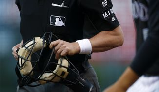 "Home plate umpire D.J. Rayburn wears a wristband to protest ""abusive player behavior"" on umpires by players as Rayburn heads to his position to call the first inning of a baseball game between the Milwaukee Brewers and and the Colorado Rockies late Saturday, Aug. 19, 2017, in Denver. (AP Photo/David Zalubowski)"