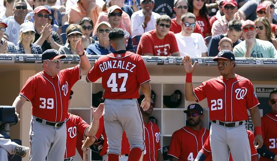 Washington Nationals starting pitcher Gio Gonzalez, center, gets congratulations from hitting coach Rick Schu (39) and catcher Pedro Severino (29) for scoring on an RBI sacrifice fly by Daniel Murphy during the third inning of a baseball game in San Diego, Sunday, Aug. 20, 2017. (AP Photo/Alex Gallardo)