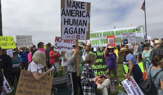 People participate in an anti-racism rally in Laguna Beach, Calif., Saturday, Aug. 19, 2017. Hundreds of people rallied at Southern California beaches to condemn racism in the wake of the deadly events in Charlottesville, Va. (Mark G. Davis via AP)
