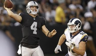 Oakland Raiders quarterback Derek Carr (4) passes as Los Angeles Rams defensive end Matt Longacre applies pressure during the first half of an NFL preseason football game in Oakland, Saturday, Aug. 19, 2017. (AP Photo/Ben Margot)