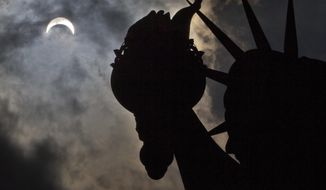 A partial solar eclipse appears over the Statue of Liberty on Liberty Island in New York, Monday, Aug. 21, 2017. (AP Photo/Seth Wenig)