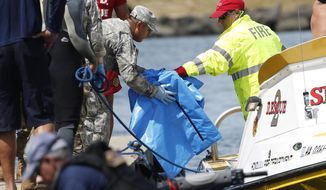 Water safety officials hand over possible debris from an Army UH-60 Black Hawk helicopter crash to military personnel stationed at a command center in a harbor, Wednesday, August 16, 2017 in Haleiwa, HI. An Army helicopter with five on board crashed several miles off Oahu's North Shore late Tuesday. Officials have suspended the search for five Army soldiers in a helicopter crash during offshore training in Hawaii on Monday, Aug. 21, 2017. (AP Photo/Marco Garcia, File)