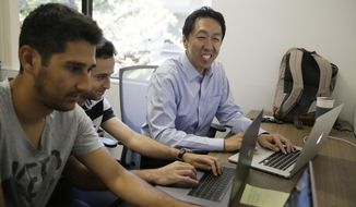 In this Friday, July 14, 2017, photo, computer scientist Andrew Ng, right, works with others at his office in Palo Alto, Calif. Ng, one of the world's most renowned researchers in machine learning and artificial intelligence, is facing a dilemma: there aren't enough experts trained to train the machines. So when he isn't pushing into the frontier of AI himself, Ng is building new ways to help educate the next generation of AI specialists. (AP Photo/Eric Risberg)