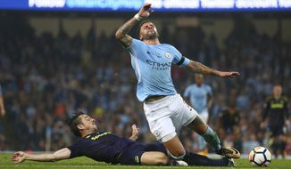 Manchester City's Kyle Walker, top, is tackled by Everton's Leighton Baines during the English Premier League soccer match between Manchester City and Everton at the Etihad Stadium in Manchester, England, Monday, Aug. 21, 2017. (AP Photo/Dave Thompson)