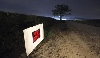 Signs warn visitors to the 350-year-old bur oak to stay on the shoulder of the road and not to venture into healthy soybean fields, outside Columbia, Mo., Sunday night, Aug. 20, 2017. Bur Oak Road, a narrow two-lane road that cuts through Missouri River bottomland, runs near the tree and is a popular spot for locals to take in nighttime spectacles. The area is expected to be a popular spot for watching Monday's solar eclipse. (Brian Kratzer/Missourian via AP)