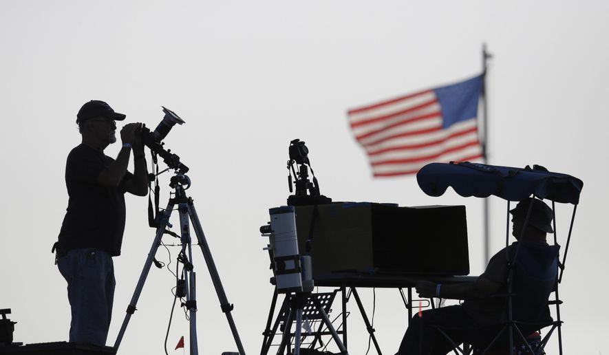 Joe Roth, left, and Scott Foster from the Chicago area are silhouetted as they prepare telescopes and cameras to observe a total solar eclipse at the base of the Bald Knob Cross of Peace, Monday, Aug. 21, 2017, in Alto Pass, Ill. (AP Photo/Charles Rex Arbogast)