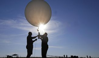 Mike Newchurch, left, professor of atmospheric chemistry at the University of Alabama in Huntsville, and graduate student Paula Tucker prepare a weather balloon before releasing it to perform research during the solar eclipse Monday, Aug. 21, 2017, on the Orchard Dale historical farm near Hopkinsville, Ky. The location, which is in the path of totality, is also at the point of greatest intensity. (AP Photo/Mark Humphrey)