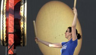 A large screen with a live telescope feed of the sun is visible behind Karen Tingey as she drums with Portland Taiko during a rehearsal in preparation for Monday's solar eclipse, in Salem, Ore., Sunday, Aug. 20, 2017. Salem is in the path of totality during the eclipse. (AP Photo/Don Ryan)
