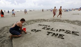 """Val Carney, from Asheville, N.C., writes in the sand in preparation for the solar eclipse Monday, Aug. 21, 2017, on the beach at Isle of Palms, S.C. The city of Isle of Palms hosted a beach party """"Get Eclipsed on IOP"""". (AP Photo/Mic Smith)"""