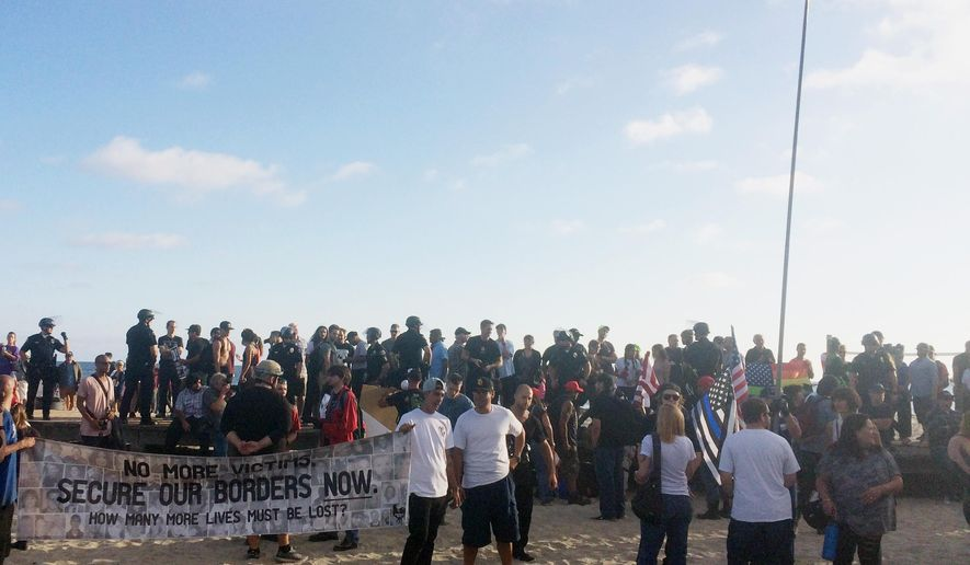 Demonstrators with flags and signs gather to protest illegal immigration, Sunday, Aug. 20, 2017, in Laguna Beach, Calif. A small group of people demonstrating against illegal immigration was outnumbered by hundreds of counterprotesters who gathered to denounce racism in the coastal California city. (AP Photo/Christopher Weber)