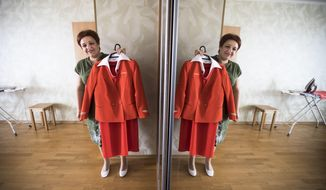 In this photo taken on Thursday, Aug. 3, 2017, Aeroflot flight attendant Yevgeniya Magurina is reflected in a mirror as she shows her uniform during an interview with the Associated Press in Lobnya, outside Moscow, Russia. The Moscow City Court is to due to rule in the case of two flight attendants who are suing Russia's flagship airline for taking them off the prestigious long-haul flights because of their looks. (AP Photo/Alexander Zemlianichenko)