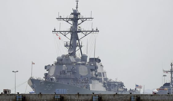 """The USS John S. McCain is seen docked at Changi naval base after its accident on Monday, Aug. 21, 2017 in Singapore. The USS John S. McCain was docked at Singapore's naval base with """"significant damage"""" to its hull (blocked by berth) after an early morning collision with the oil tanker Alnic MC as vessels from several nations searched Monday for missing U.S. sailors. (AP Photo/Wong Maye-E)"""