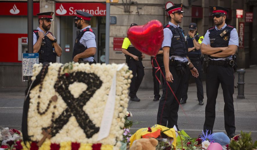 Police officers stand guard next to flags, flowers, messages and candles to the victims on Barcelona's historic Las Ramblas promenade on the Joan Miro mosaic, embedded in the pavement where the van stopped after killing at least 14 people in Barcelona, Spain, Monday, Aug. 21, 2017. (AP Photo/Emilio Morenatti)