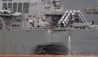 The damaged port aft hull of the USS John S. McCain, is visible while docked at Singapore's Changi naval base on Tuesday, Aug. 22, 2017 in Singapore. The focus of the search for the U.S. sailors missing after a collision between the USS John S. McCain and an oil tanker in Southeast Asian waters shifted Tuesday to the damaged destroyer's flooded compartments. (AP Photo/Wong Maye-E)