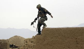 FILE - In this Nov. 1, 2009 file photo, a U.S. special operations forces servicemember climbs down from a compound wall after investigating suspicious activity, during a joint patrol with Afghan National Army soldiers in Shewan, a former Taliban Stronghold, in Afghanistan's Farah province. Reversing his past calls for a speedy exit, President Donald Trump recommitted the United States to the 16-year-old war in Afghanistan, declaring Monday, Aug. 21, 2017 U.S. troops must fight to win. He pointedly declined to disclose how many more troops will be dispatched to wage Americas longest war. (AP Photo/Maya Alleruzzo)