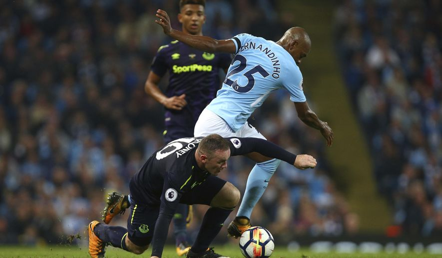 Manchester City's Fernandinho, right, and Everton's Wayne Rooney battle for the ball during the English Premier League soccer match between Manchester City and Everton at the Etihad Stadium in Manchester, England, Monday, Aug. 21, 2017. (AP Photo/Dave Thompson)
