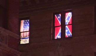 This Aug. 17, 2017 image from video shows a Confederate flag, right, displayed alongside an Israeli flag and a colonial-era American one in the seventh-floor windows of an apartment in the East Village neighborhood of New York. The flags had been there for over a year, and illuminated at night, but after an Aug. 12 white nationalist rally to preserve a Confederate statue in Charlottesville, Va., spiraled into violence the flags were met with hurled rocks, a punched-out window, a tarp hung over them and legal action before being removed. (PIX11 News via AP)