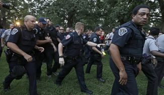 """Police arrest a man during a protest at a Confederate monument at the University of North Carolina in Chapel Hill, N.C., Tuesday, Aug. 22, 2017. The gathering Tuesday night at the university focused on a statue known as """"silent Sam."""" People chanted """"tear it down"""" while uniformed officers watched from behind temporary metal barriers ringing the statue, depicting a Confederate soldier. (AP Photo/Gerry Broome)"""