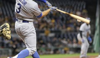 Los Angeles Dodgers' Chris Taylor drives in Yasiel Puig, right, on third with a base hit during the fourth inning of a baseball game against the Pittsburgh Pirates, Tuesday, Aug. 22, 2017, in Pittsburgh. (AP Photo/Keith Srakocic)