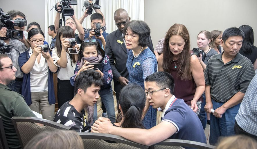 Lifeng Ye, seated-center, is comforted by her son Xinyang Zhang, left, and Xiaolin Hou, right, after a news conference at the I-Hotel in Urbana, Ill., Tuesday Aug. 22, 2017. Lifeng Ye, is the mother, Xinyang Zhang is the younger brother, and Xiaolin Hou is the boyfriend of visiting Chinese scholar Yingying Zhang who went missing on June 9. (Rick Danzl/News-Gazette via AP)