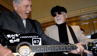 """FILE - In this March 20, 2009 file photo, rockabilly musician Albert """"Sonny"""" Burgess, right, and Arkansas Gov. Mike Beebe jam on guitars before a bill-signing at the Capitol in Little Rock, Ark. Burgess, who was an early pioneer of what became known as rockabilly music, died Friday, Aug. 18, 2017, in Little Rock. He was 88. (AP Photo/Mike Wintroath, File)"""
