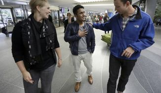 Army Capt. Matthew Ball (right), with wife Giselle Rahn, welcomed Qismat Amin to California. Amin, who worked as a translator for the U.S. military in Afghanistan from 2010 to 2015, is one of the few lucky allies who have been able to immigrate to the U.S. (Associated Press/File)