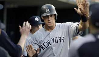 New York Yankees' Aaron Judge is greeted in the dugout after scoring from second on a single by teammate Tyler Austin during the third inning of a baseball game against the Detroit Tigers, Tuesday, Aug. 22, 2017, in Detroit. (AP Photo/Carlos Osorio)