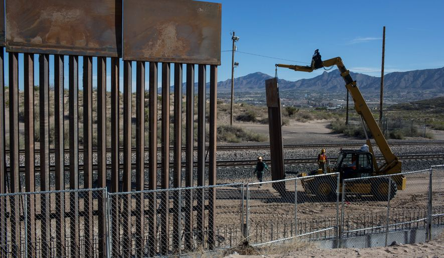 In this  March 30, 2017 file photo, Workers use a crane to lift a segment of a new fence into place on the U.S. side of the border with Mexico, where Sunland Park, New Mexico, meets the Anapra neighborhood of Ciudad Juarez, Mexico. (Associated Press) **FILE**