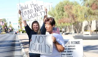 Cliven Bundy's daughter, Bailey Bundy Logue (left) and Margaret Houston wave signs in front of the Lloyd George U.S. Courthouse in Las Vegas after the not guilty verdict in the retrial Tuesday. (Associated Press)