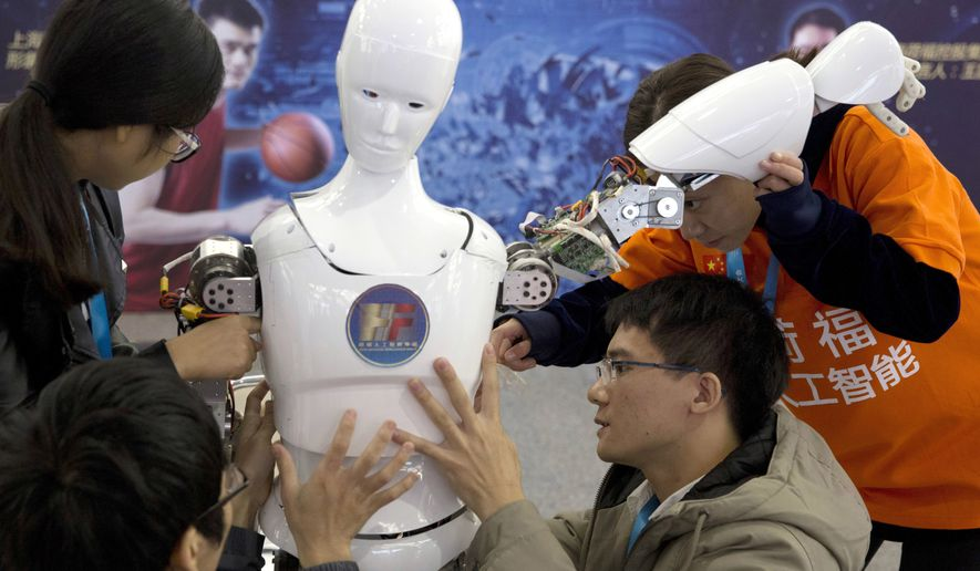 Chinese students work on the Ares, a humanoid bipedal robot designed by them with fundings from a Shanghai investment company, displayed during the World Robot Conference in Beijing. China's government announced Thursday, July 21, 2017, a goal of transforming the country into a global leader in artificial intelligence in just over a decade, putting additional political support behind growing investment by Chinese companies in developing self-driving cars and other advances. (AP Photo/Ng Han Guan, File)