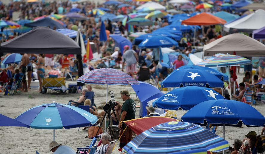 """David Nash, in green shirt with camera on tripod, works with his camera during the solar eclipse Monday, August 21, 2017, on the beach at Isle of Palms, S.C. """"I'm hoping for three minutes of clear, but we'll see what happens"""", a nervous Nash said as cloud cover hung over the Isle of Palms. (AP Photo/Mic Smith)"""
