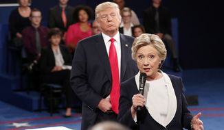 FILE - In this Oct. 9, 2016 file photo, Democratic presidential nominee Hillary Clinton, right, speaks as Republican presidential nominee Donald Trump listens during the second presidential debate at Washington University in St. Louis, Sunday, Oct. 9, 2016. (Rick T. Wilking/Pool via AP)