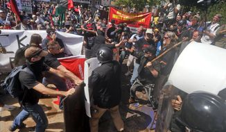 In this Aug. 12, 2017 file photo, white nationalist demonstrators clash with counter demonstrators at the entrance to Lee Park in Charlottesville, Va. (AP Photo/Steve Helber, File) **FILE**