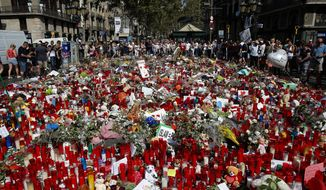 People stand next to candles and flowers placed on the ground, after a terror attack that left many killed and wounded in Barcelona, Spain, Wednesday, Aug. 23, 2017.   Police in northeastern Spain said Wednesday they have found a belt charged with real explosives in a house used by the Barcelona attacks extremist cell.  (AP Photo/Manu Fernandez)