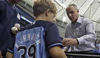 Baseball Commissioner Rob Manfred, right, signs autographs for fans while on his way to a news conference before a baseball game between the Tampa Bay Rays and the Toronto Blue Jays on Wednesday, Aug. 23, 2017, in St. Petersburg, Fla. (AP Photo/Chris O'Meara)