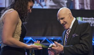"""FILE – In this Feb. 15, 2017, file photo, retired professional wrestler Bruno Sammartino examines U.S. rower Amanda Polk's Olympic gold medal at the 81st Dapper Dan Awards and sports auction, a fundraiser for the Boys & Girls Clubs of Western Pennsylvania, in Pittsburgh. Sammartino met with pop singing sensation Bruno Mars on Tuesday, Aug. 22, 2017, when Mars' 24K Magic World Tour stopped in Pittsburgh, after Sammartino heard Mars was nicknamed """"Bruno"""" as a baby because Sammartino was Mars' father's favorite wrestler. (Haley Nelson/Pittsburgh Post-Gazette via AP, File)"""