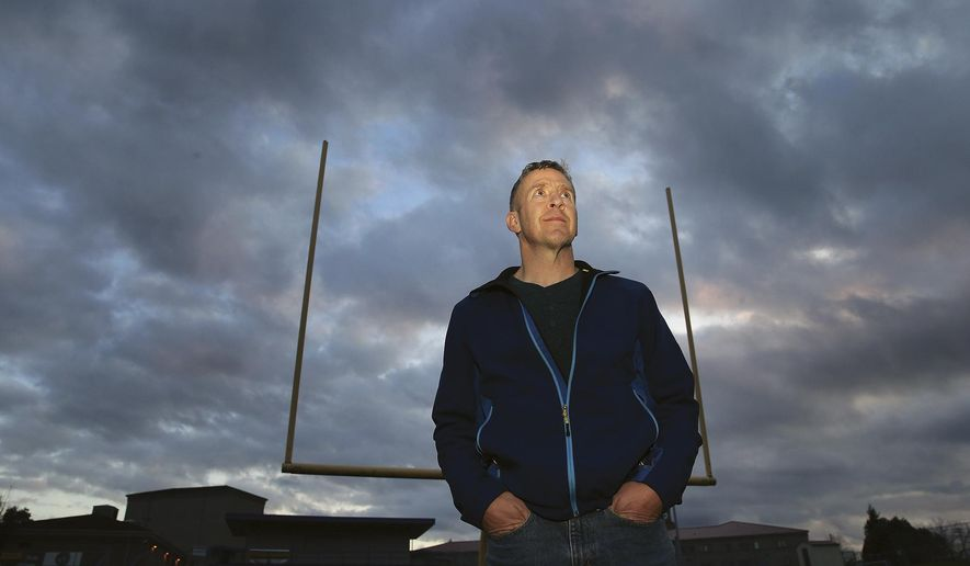 In this Nov. 5, 2015, photo, former Bremerton High School assistant football coach Joe Kennedy poses for a photo at Bremerton Memorial Stadium in Bremerton, Wash. A federal appeals court ruled Wednesday, Aug. 23, 2017, that the Bremerton School District does not have to immediately re-hire Kennedy, who lost his job after refusing to stop leading players in prayer on the football field after games. (Larry Steagall/Kitsap Sun via AP) **FILE**