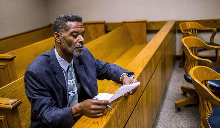 Flint City Councilman Eric Mays looks over paperwork before Judge William H. Crawford arraigns him on Wednesday, Aug. 23, 2017, in Genesee District Court  on Wednesday, Aug. 23, 2017, in Flint, Mich. Mays followed by pleading no contest to a misdemeanor charge of willful neglect by a public official, in relation to allegedly pawning a city-issued laptop nine time in the last two years.Mays will not be sentenced until after the November election. (Jake May/The Flint Journal-MLive.com via AP)